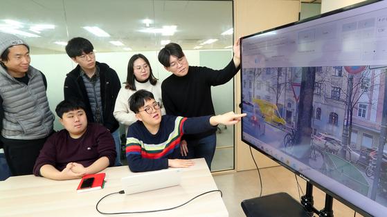 발달장애인 김지욱(앞줄 왼쪽)ㆍ김상현(앞줄 오른쪽), 청각장애인 김현기(뒷줄 왼쪽 첫번째)ㆍ이은비(뒷줄 왼쪽에서 세번째)씨가 비장애인 직원들과 함께 화면을 보며 회의를 하고 있다. 변선구 기자