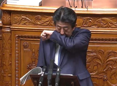 아베 신조(安倍晋三) 일본 총리가 6일 오전 참의원 본회의에서 답변서를 읽던 중 기침이 나오려하자 소매로 입을 가리고 있다. 연합뉴스