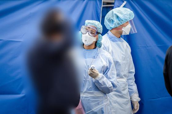 선별진료소를 찾은 한 환자가 통증을 호소하는 듯 머리카락을 움켜잡은 채 의료진으로부터 설명을 듣고 있다. 사진 대구가톨릭대병원