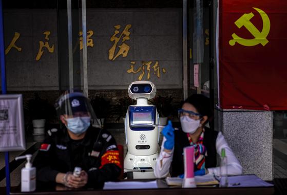 지난 달 26일 중국 광둥성 광저우의 한 관공서 출입구에서 인공지능(AI)로봇이 지나가는 사람들의 열을 자동으로 감지하고 있다. 이 로봇은 최대 10명의 체온을 한꺼번에 측정할 수 있다. [EPA=연합뉴스]