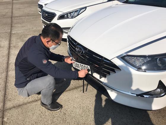 8일 오전 제주도내 한 렌터카 업체 직원이 차량에서 번호판 떼어 내고 있다. 최충일 기자