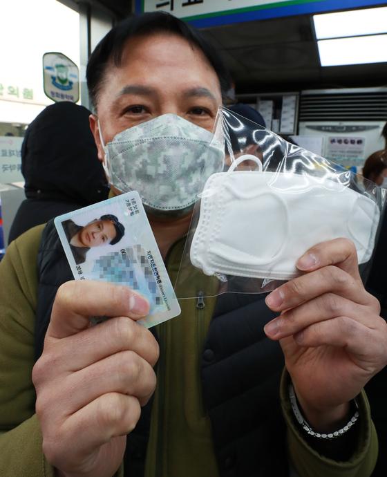 마스크 5부제가 시행된 9일 오전 서울 종로구의 한 약국에서 시민들이 신분증을 제시하며 마스크를 구매하고 있다. 마스크 5부제 시행으로 약국에서 출생년도에 따라 1주당 1인 2매 구매가 가능하다. 최정동 기자