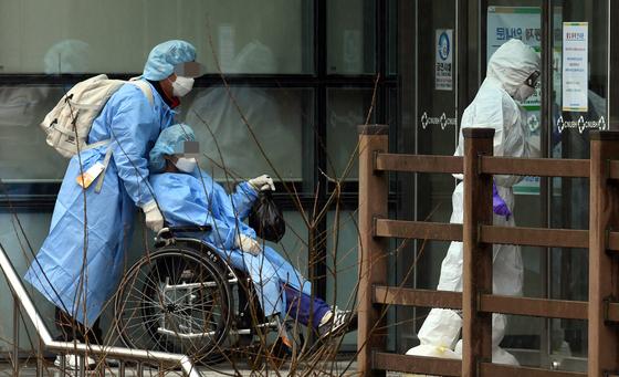 코로나19 대구지역 확진자들이 119구급차량을 이용해 7일 오후 광주 남구 광주감염병전문병원인 빛고을전남대병원에 도착한 뒤 의료진의 안내를 받으며 병실로 향하고 있다. 뉴시스