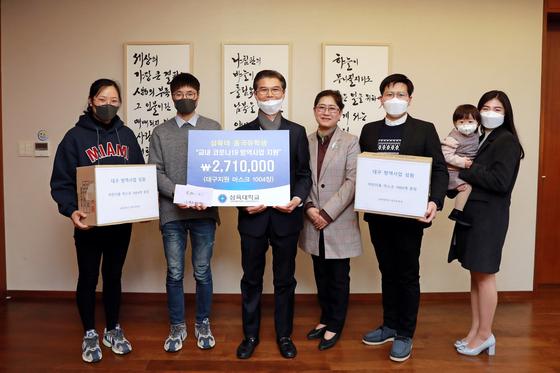 삼육대 중국인 유학생들이 김일목 총장(왼쪽에서 세 번째)과 김정숙 대외협력처장(네 번째)에게 교내 방역사업 지원금과 대구 지원 마스크 1004장을 전달하고 있다.