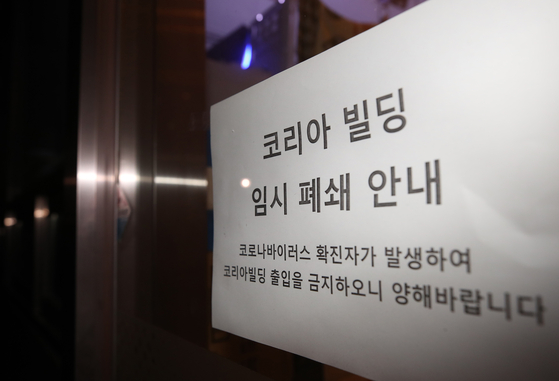 서울 구로구 신도림동 코리아빌딩 11층에 있는 콜센터에서 집단 감염 사례로 추정되는 코로나19 확진자가 무더기로 발생했다고 구로구가 밝힌 9일 해당 건물 앞에 임시 폐쇄 관련 안내문이 붙어 있다. 연합뉴스