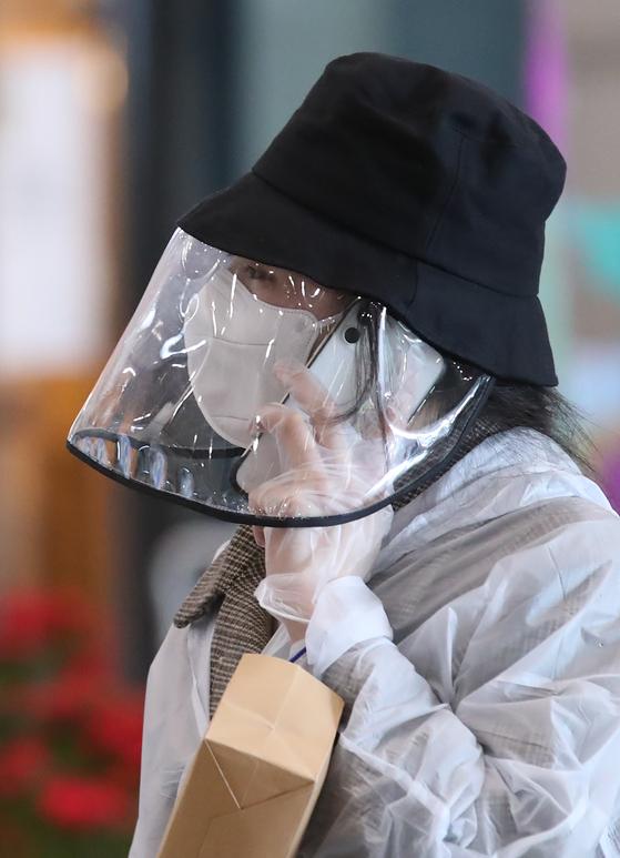 지난달 24일 인천국제공항 1터미널에서 입국한 한 중국인 유학생이 모자와 마스크, 얼굴 가리개, 비닐장갑과 우의 등으로 몸을 가린 채 휴대전화로 통화를 하고 있다. [연합뉴스]