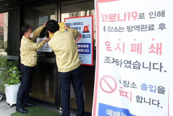 전북도 직원들이 지난달 26일 행정명령에 따라 전주시 경원동에 있는 신천지교회 부속시설에 '임시폐쇄' 스티커를 붙이고 있다. 연합뉴스