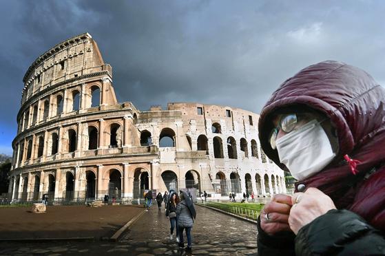 지난 7일 이탈리아 로마의 콜로세움 앞에서 한 관광객이 마스크를 쓴 채 옷깃을 여미고 있다. [AFP=연합뉴스]