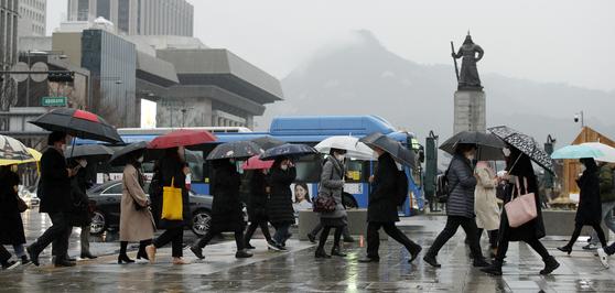 지난달 25일 봄비가 내리는 오전, 서울 종로구 광화문 네거리에서 마스크와 우산을 쓴 시민들이 출근하고 있는 모습. 10일도 전국에 비가 내리고 오후들어 남부지방부터 서서히 그칠 예정이다. [뉴스1]