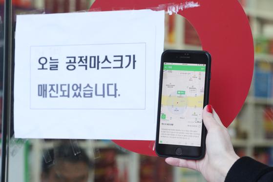 마스크 현황 애플리케이션(앱) 서비스가 시작된 11일 오전 서울 광화문광장 인근 한 약국 앞에서 시민이 앱을 통해 마스크 충분 상태를 확인한 뒤 방문했으나 마스크 품절 안내문이 붙어 있다. [연합뉴스]