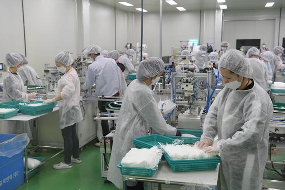 6일 경기도 평택의 마스크 제조공장인 우일씨앤텍에서 직원들이 마스크 생산에 박차를 가하고 있다. [청와대사진기자단]