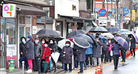 마스크 5부제 시행 이틀째인 10일 오후 서울 주택가의 한 약국 앞에서 우산을 쓴 주민이 공적 마스크를 구매하기 위해 줄을 서 있다. 연합뉴스
