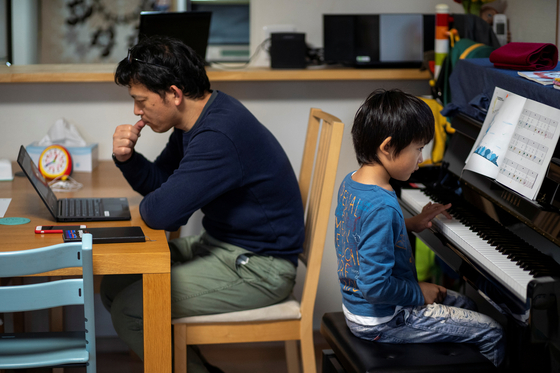 일본에서 휴교 조치가 취해지면서 가정에서 아이를 돌보는 시간이 늘어나게 됐다. 아버지가 재택근무를 하는 동안 휴교 중인 아들은 집에서 피아노를 연습하는 모습. [로이터=연합뉴스]