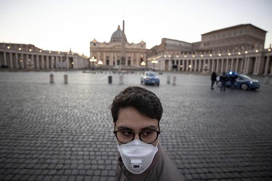 11일 신종 코로나 감염증(코로나19) 사태로 인해 이탈리아 로마의 성베드로성당에 사람들의 발길이 끊긴 가운데, 마스크를 쓴 한 시민이 성당 앞을 지나가고 있다. [EPA=연합뉴스]