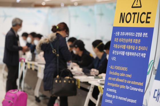 9일 인천국제공항 2터미널에 도착한 승객들이 검역 등의 특별입국절차를 거치고 있다. [연합뉴스]