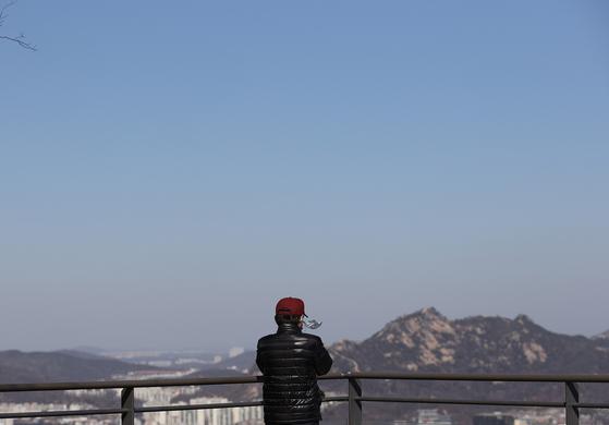 11일 오전 서울 중구 남산을 찾은 한 시민이 시내를 내려다보고 있다. 토요일인 14일은 전국이 맑고 공기도 깨끗하지만, 꽃샘추위로 인해 쌀쌀한 날씨가 예상된다. [연합뉴스]