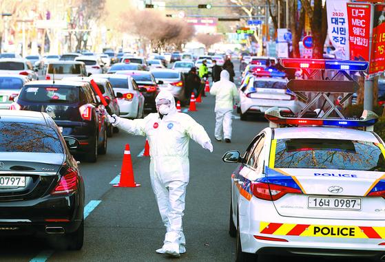 대구에서 방호복을 입은 한 경찰관이 병원 앞에서 주변 교통을 통제하며 환자 이송 준비를 하고 있다. 뉴스1
