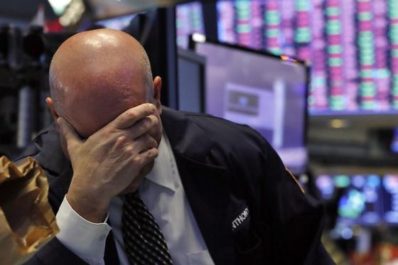 13일(현지시간) 미국 뉴욕증권거래소(NYSE). 한 트레이더가 손으로 얼굴을 가리고 있다. 연합뉴스