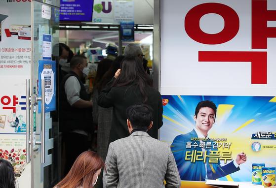 13일 오후 서울 시내의 한 약국에서 시민들이 마스크를 구매하기 위해 줄을 서고 있다. [연합뉴스]