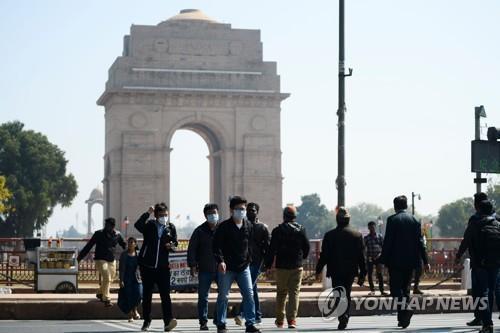 마스크를 쓰고 인도 뉴델리 시내 인디아게이트 앞을 지나는 사람들. AFP=연합뉴스