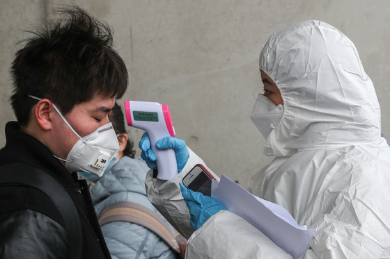 신종 코로나바이러스감염증(코로나19) 확산세가 급증하고 있는 지난달 25일 오후 중국인 유학생들이 인천국제공항 입국장을 통해 입국해 대학 관계자로부터 체온 검사를 받고 있다.[뉴스1]