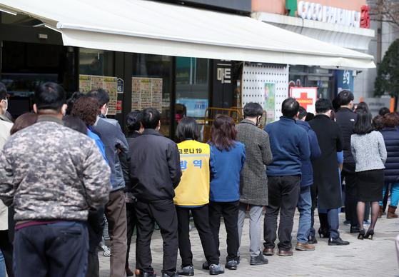 12일 서울 중구 명동의 한 약국 앞에서 시민들이 공적 마스크를 사기 위해 기다리고 있다. [연합뉴스]