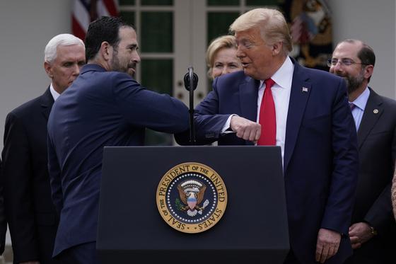 트럼프 대통령이 13일 백악관에서 그린스타인 LHC 부사장과 팔꿈치 인사를 하고 있다.뉴시스