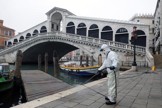 전국 봉쇄령으로 인적이 끊긴 이탈리아 베니스의 리알토 다리 아래에서 방역요원이 소독 작업을 하고 있다.평소 길을 걸어다니기도 힘들 정도로 수많은 인파가 몰리던 관광 명소다. 로이터=연합뉴스,