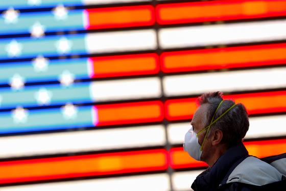 미국 뉴욕 맨해튼에서 13일 한 남성이 마스크를 쓰고 지나가고 있다. 14일 현재 미국 내 49개주에서 코로나19 확진자가 나왔다. [로이터=연합뉴스]
