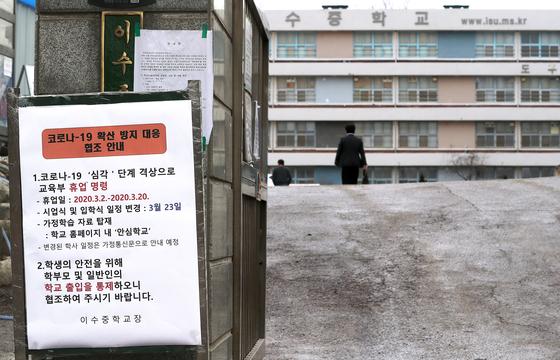 코로나19 확산세가 지속되자 2일 교육부는 전국 유치원과 초·중·고 개학을 오는 23일로 연기하기로 결정했다. 3일 서울 서초구 이수중학교 정문에 '휴업 명령' 안내문이 붙어 있다. [연합뉴스]