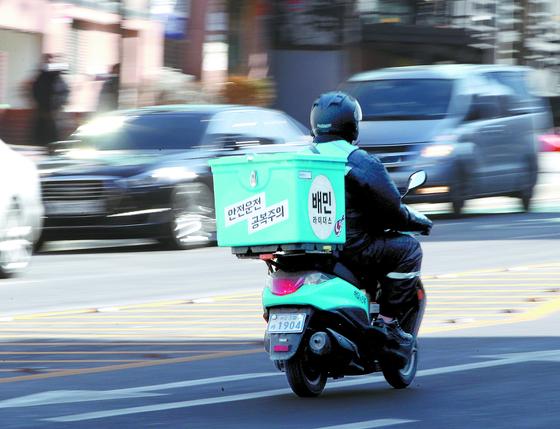 코로나 이후 부업으로 오토바이 배달업에 입문하는 이들이 늘고 있다. 사진은 오토바이 배달 중인 배민라이더스 소속의 배달맨. 뉴스1