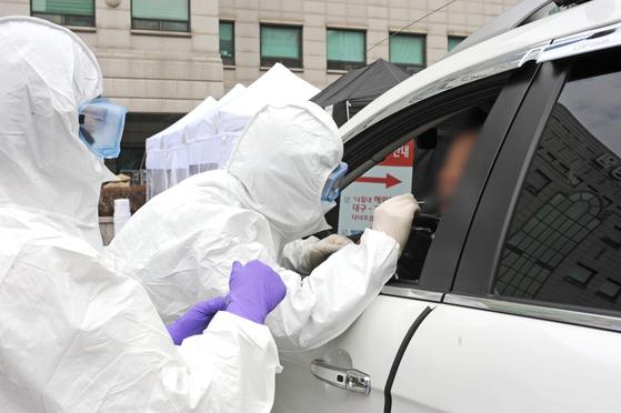차에 탄 채로 코로나 19 검사를 받는 선별 진료소. 연합뉴스