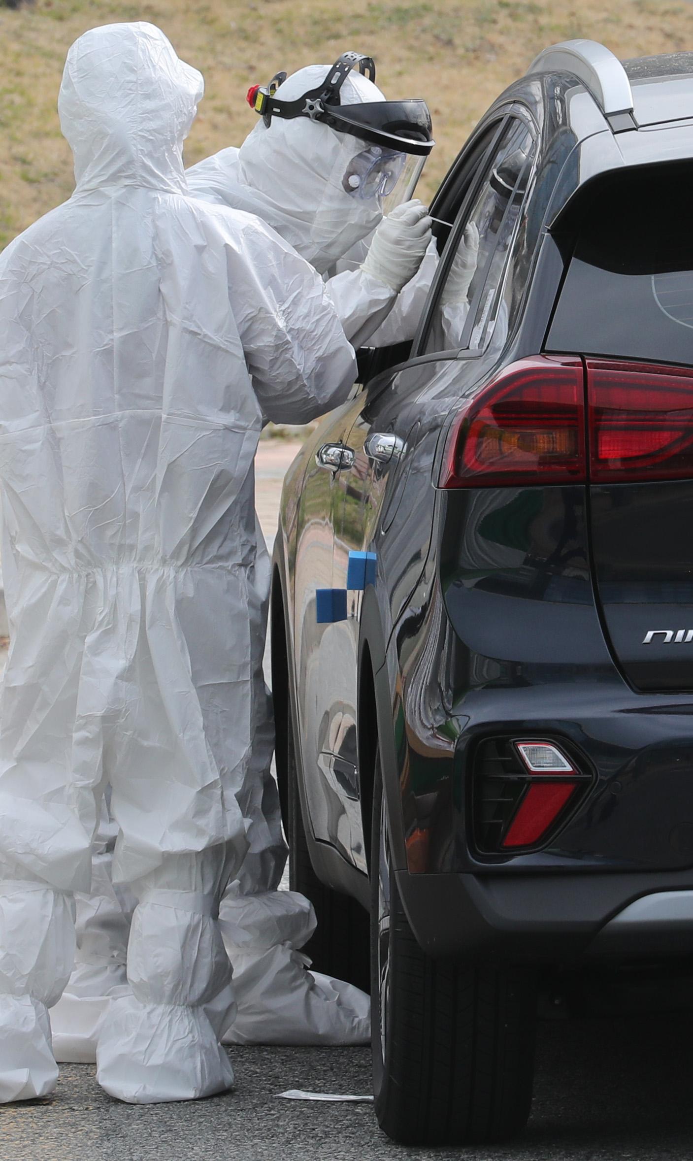 13일 세종시 정부세종청사에 설치된 드라이브 스루 선별진료소에서 의료진이 자동차 탑승자의 검체를 채취하고 있다. 연합뉴스