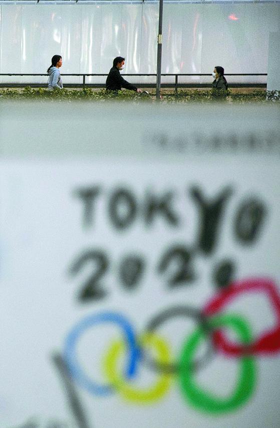 신종 코로나바이러스 감염증(코로나19)가 전 세계로 확산하면서 올림픽 취소 가능성이 높아지고 있다. 지난 3일 일본 도쿄 시민들이 마스크를 쓴 채 걸어가고 있다. AP=연합뉴스