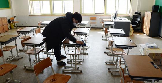 신종 코로나바이러스 감염증(코로나19)의 여파로 전국의 학교가 휴업한 2일 전북 전주시 전주동초등학교에서 한 교사가 책상을 닦고 있다. [뉴시스]