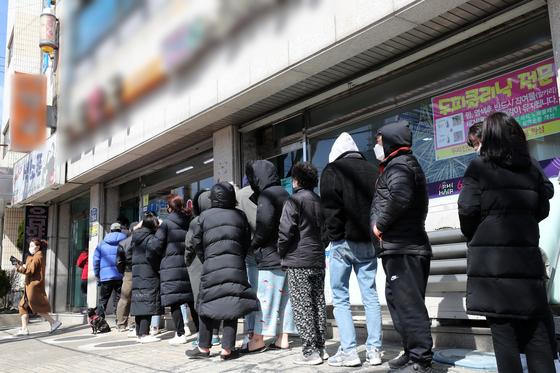 지난 15일 오후 경기도 수원시내 한 약국 앞에서 시민들이 마스크를 구매하기 위해 길게 줄 서 있다. [뉴스1]