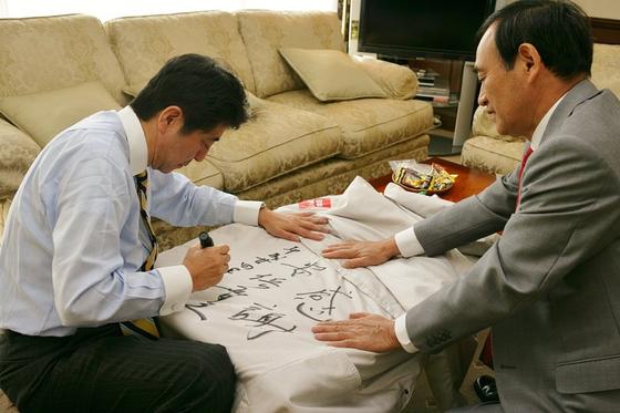 지난 2012년 12월 중의원 선거운동 당시 아베 총리가 한 선거운동원의 코트에 짧은 글을 남기는 모습. 스가 장관이 옆에서 옷감을 평평하게 잡아주고 있다. [아베 총리 페이스북]