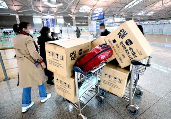 지난달 3일 오후 인천국제공항 1터미널에서 중국인 여행객들이 마스크 박스가 실린 카트를 밀고 탑승수속대로 향하고 있다. 연합뉴스.