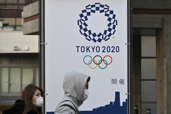 일본 요코하마 시민들이 마스크를 쓰고 도쿄올림픽 배너 앞을 지나가고 있다. [AFP=연합뉴스]