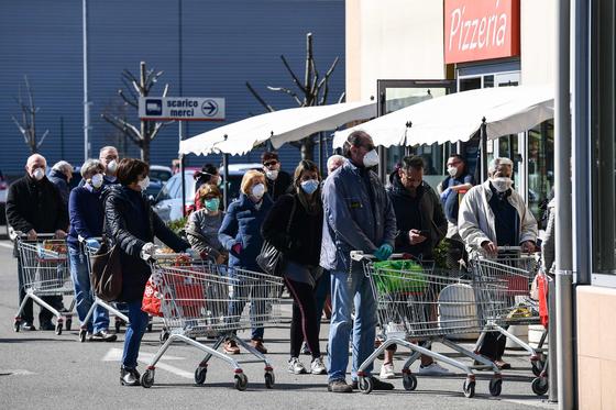 이탈리아에서 전례 없는 전국 이동제한령이 발효된 다음날인 지난 11일(현지시간) 밀라노 인근 소도시 코도뇨의 한 슈퍼마켓 앞에서 마스크를 쓴 주민들이 줄을 서서 입장을 기다리고 있다. AFP=연합뉴스