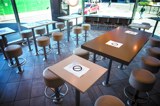 뉴욕의 카페 등이 폐쇄된 가운데 16일 맥도날드 매장에 띄어 앉으라는 경고문이 탁자에 부착돼 있다. [신화=연합뉴스]