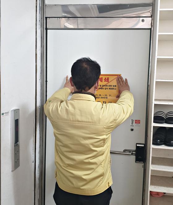 충북 충주시가 신종 코로나바이러스 감염증(코로나19) 확산 차단을 위해 신천지 관련 시설 33개소를 폐쇄했다고 12일 밝혔다.  사진은 시설폐쇄 안내문을 붙이는 모습. 연합뉴스