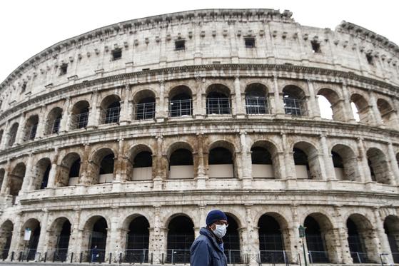 13일 이탈리아 로마의 콜로세움 앞을 마스크를 쓴 남성이 지나가고 있다. 신종 코로나 사태 이후 이탈리아의 관광산업은 마비 상태다. [AP=연합뉴스]
