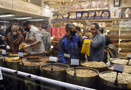 이란 새해 명절 누루즈를 앞둔 지난 18일 이란 테헤란의 한 시장에서 이란인들이 마스크와 장갑을 착용한 채 장을 보고 있다.[EPA=연합뉴스]