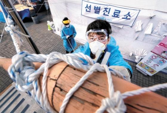 서울 마포구 보건소 선별진료소 의료진이 예보된 강풍에 대비하기 위해 18일 오후 끈으로 시설을 고정하고 있다. 뉴시스