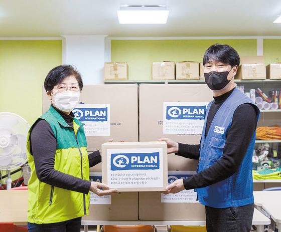 플랜코리아 관계자(오른쪽)가 지난 5일 경기도 김포시의 아동보호센터를 방문해 코로나19 확산 방지를 위해 마스크·손소독제 등이 든 위생용품 박스를 전달하고 있다. [사진 플랜코리아]