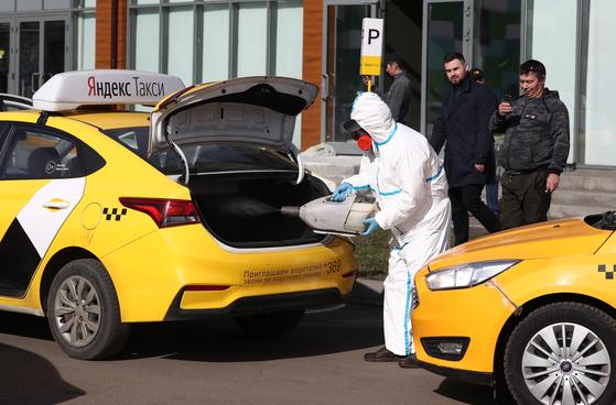 러시아 수도 모스코바에서 한 방역요원이 택시를 소독하고 있다. 타스=연합뉴스