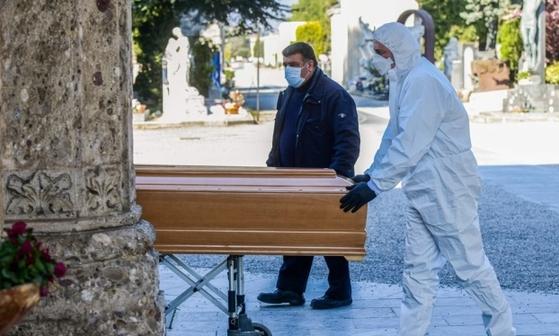 이탈리아 롬바르디아 주 베르가모의 공동묘지에서 장의사가 사망자의 관을 옮기고 있다. AFP=연합뉴스