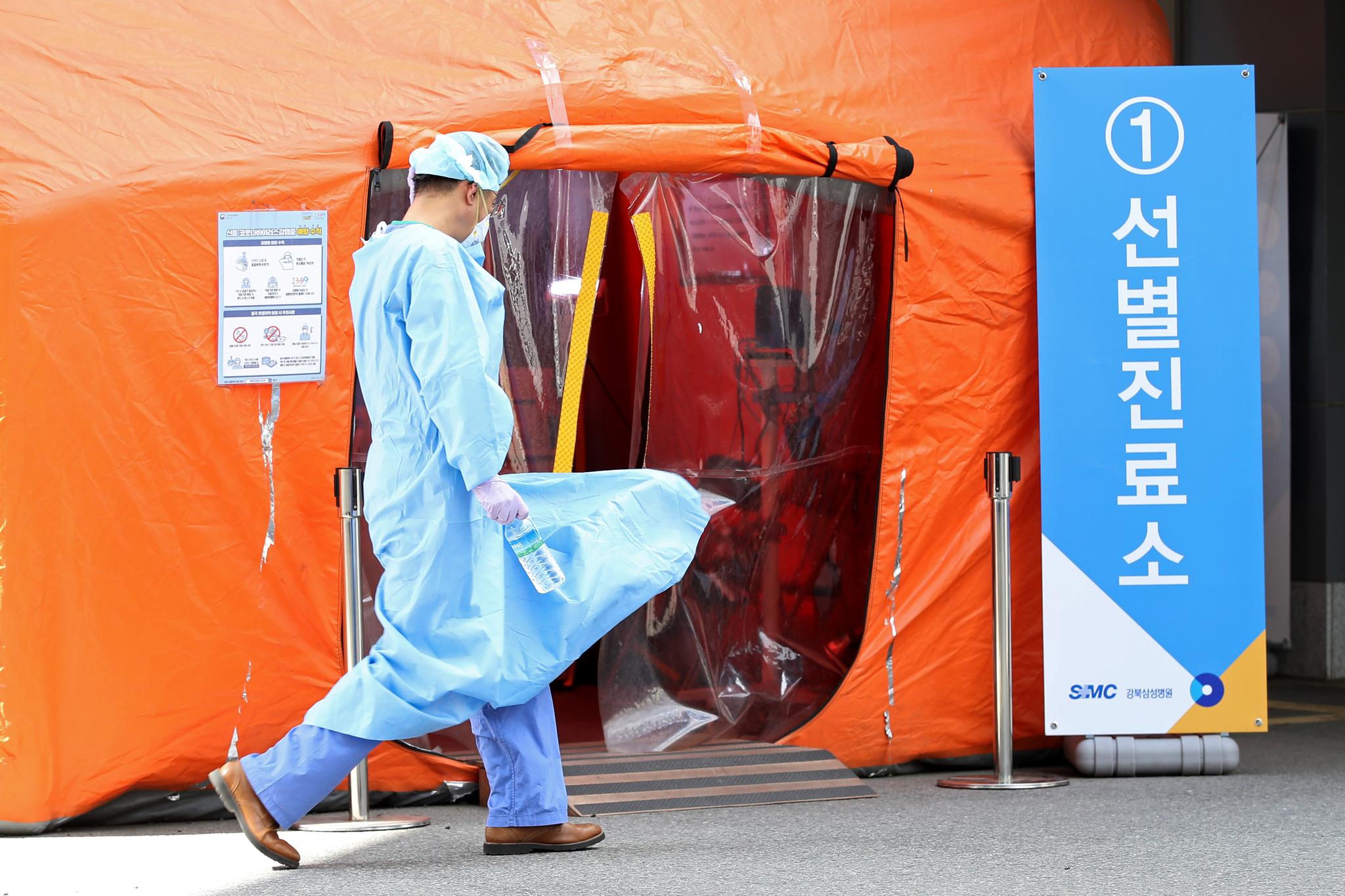 전국에 강풍 경보가 발효된 19일 오후 서울 종로구 강북삼성병원에 마련된 선별진료소 앞을 지나가는 의료진의 의료가운이 바람에 펄럭이고 있다. 연합뉴스