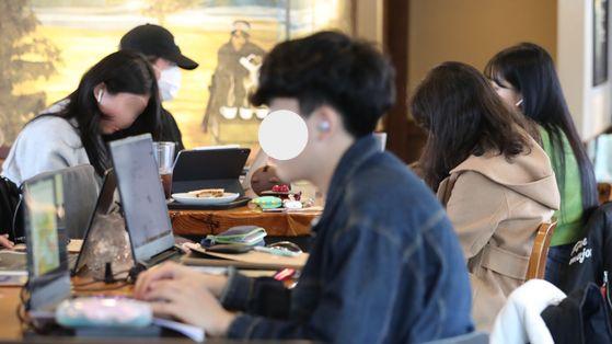 서울 주요대학이 온라인 강의를 실시한 지 이틀 째인 17일 오후 서울 마포구 홍익대학교 인근 한 카페에서 대학생 및 시민들이 시간을 보내고 있다. [연합뉴스]